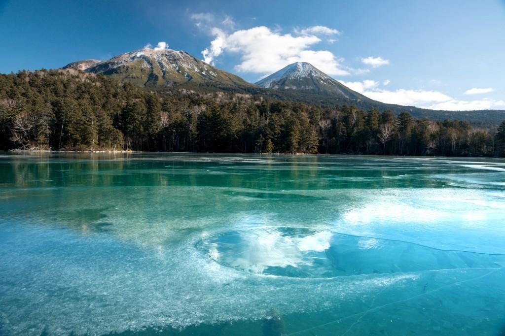 オンネトーの氷と反射する山